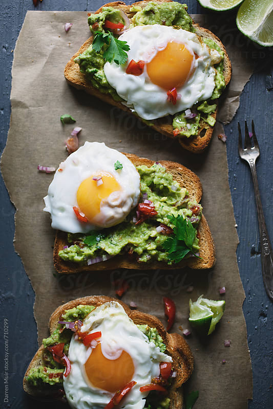 Avocado toasts with soft fried eggs on brown paper on a table. by Darren Muir for Stocksy United