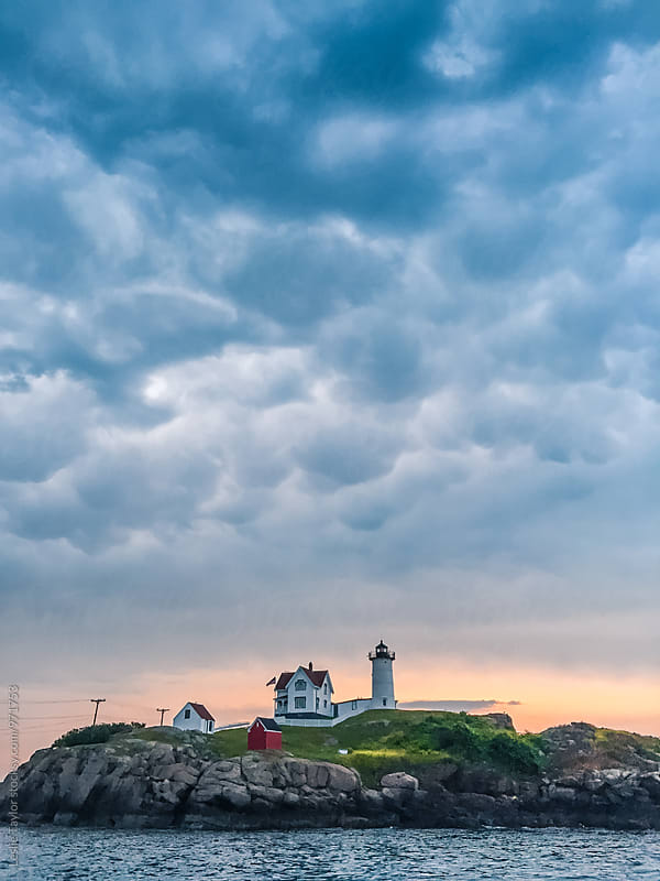 Nubble Lighthouse With A Cloudy Sunrise by Leslie Taylor for Stocksy United