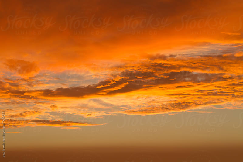 fiery clouds at sunset by Jess Lewis for Stocksy United