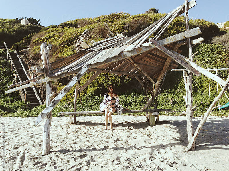 Woman Sitting Under Beach Hut by Kevin Russ for Stocksy United