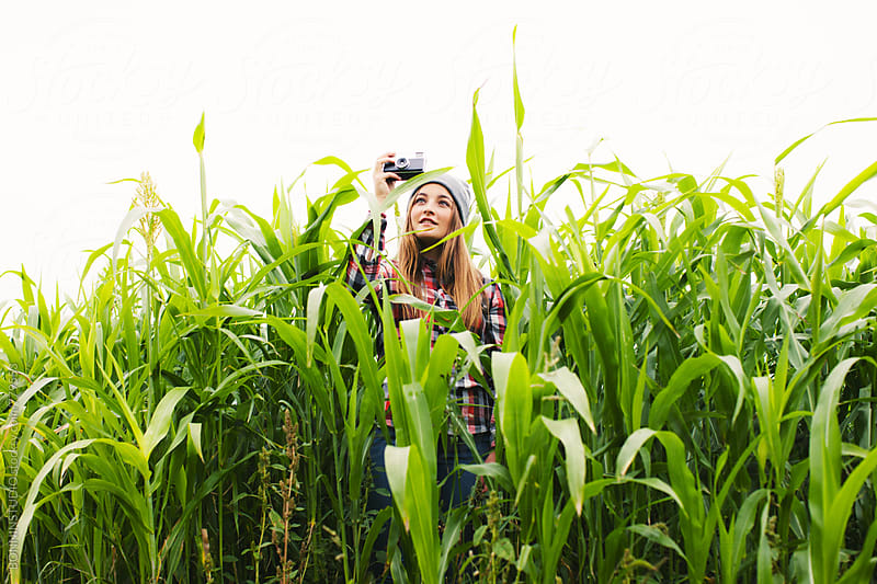 Teen girl taking a photo standing between a corn field. by BONNINSTUDIO for Stocksy United