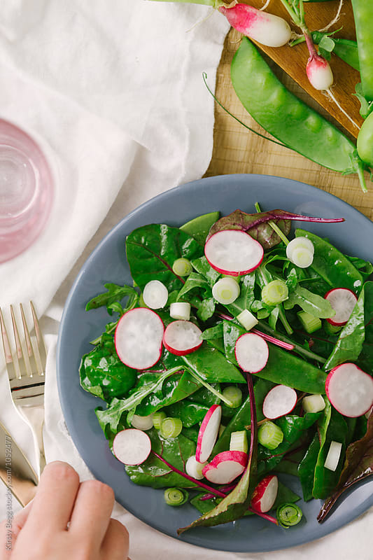 Woman picks up fork to eat fresh salad with radish and pea by Kirsty Begg for Stocksy United