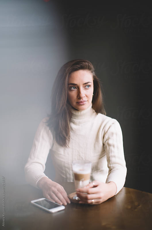 portrait of real woman sitting in a Coffee Shop.  by Vesna for Stocksy United