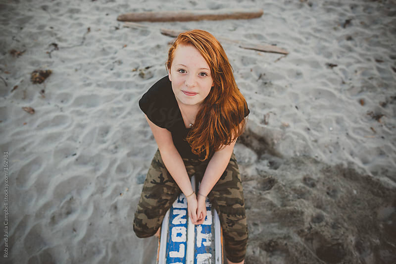 Content portrait of redhead teenage girl sitting at the beach by Rob and Julia Campbell for Stocksy United