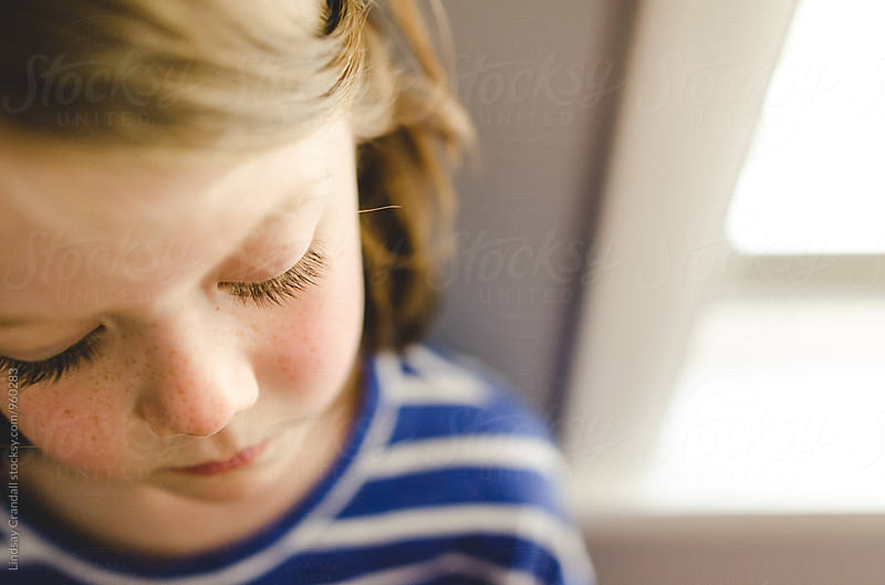 Closeup of young child standing beside a window by Lindsay Crandall for Stocksy United