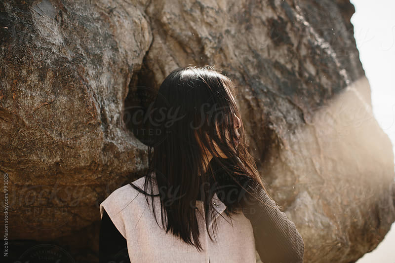woman standing against rock at coast with hair over her face by Nicole Mason for Stocksy United