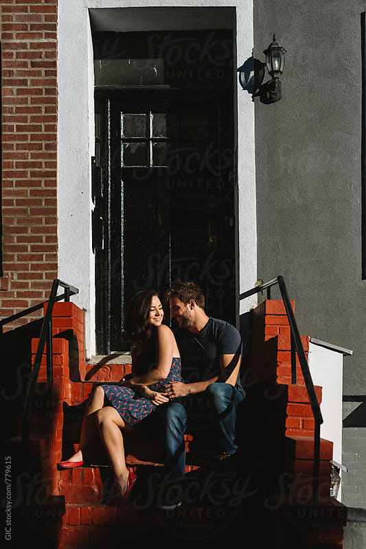Young couple sitting on the stairs by Simone Becchetti for Stocksy United