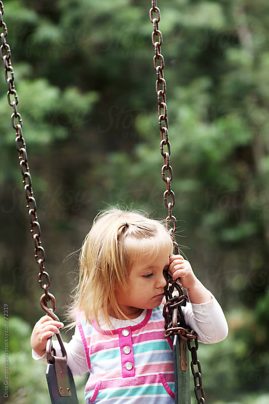 Toddler on swing looking to side sad or tired by Dina Giangregorio for Stocksy United