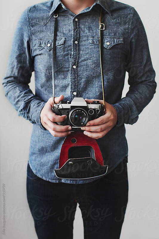 Man holding a vintage camera by Ellie Baygulov for Stocksy United