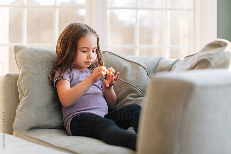 Cute young girl sitting on a chair putting a band on her finder by Jakob for Stocksy United