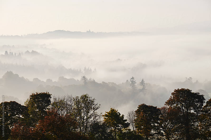 Layers of fog in the valley at sunrise. Troutbeck, Cumbria, UK. by Liam Grant for Stocksy United