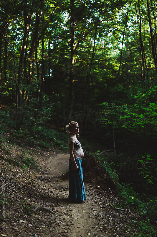 Pregnant woman standing in the forest by michela ravasio for Stocksy United