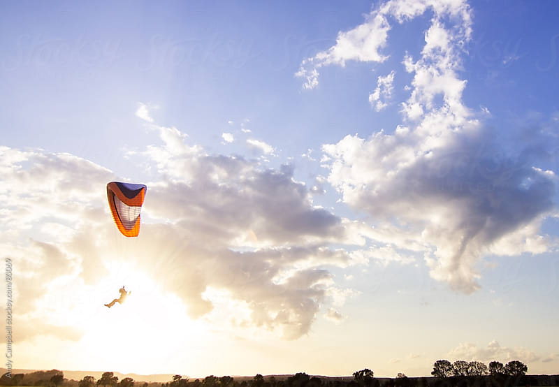 A paraglider flies past the sun by Andy Campbell for Stocksy United
