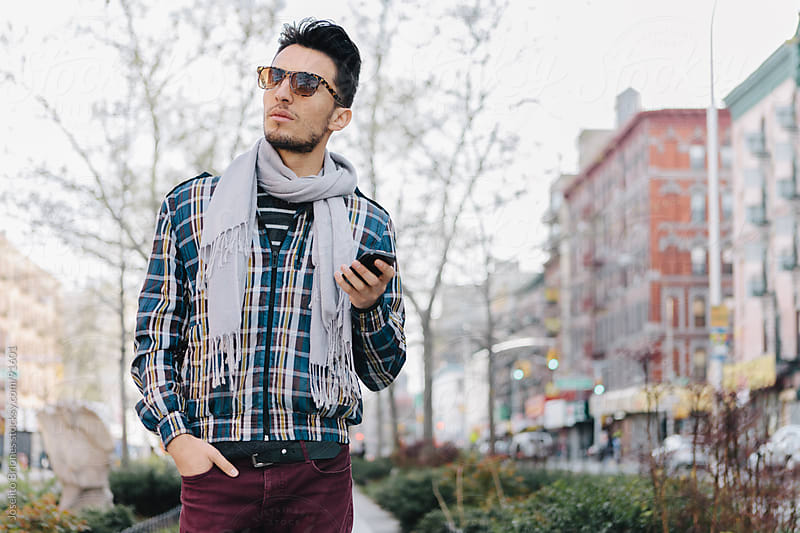 Hip Urban Young Man Texting on Smart Phone by Joselito Briones for Stocksy United