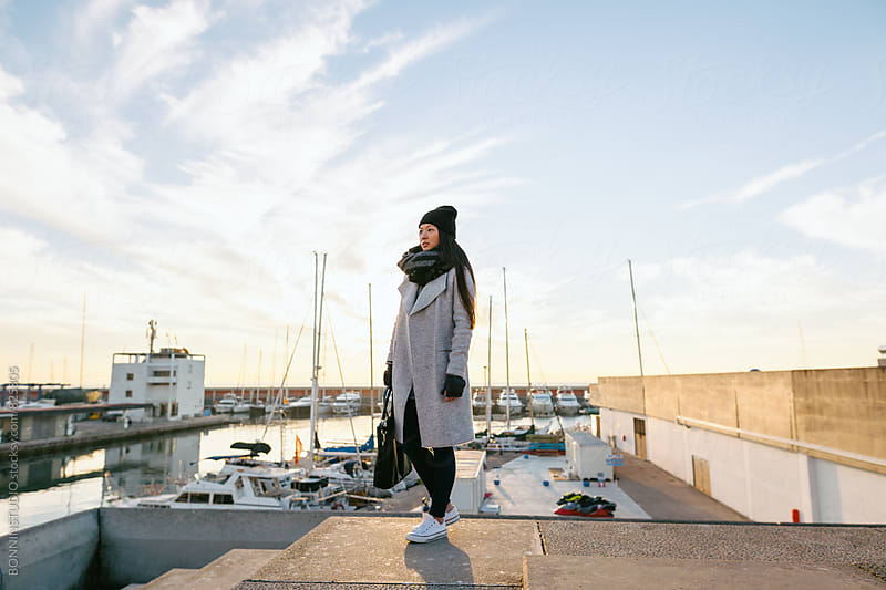 Chic chinese woman standing on a seaport at sunrise. by BONNINSTUDIO for Stocksy United