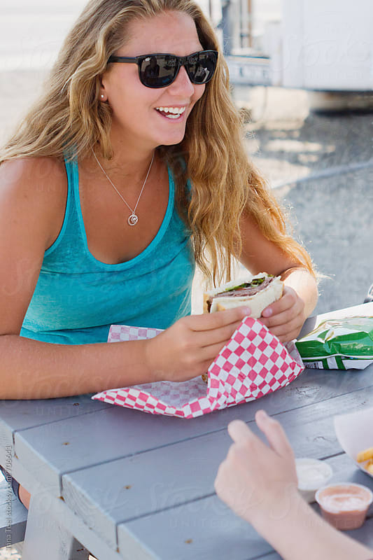 smiling customer holds sandwich while sitting in shade by Tana Teel for Stocksy United