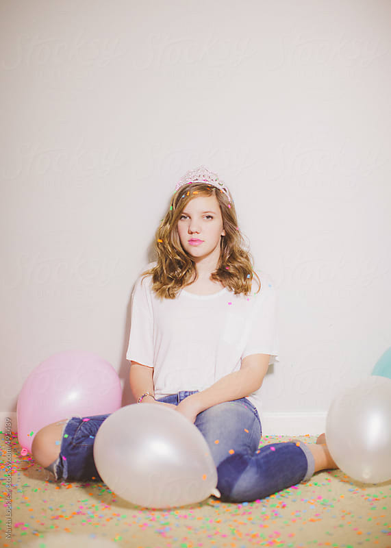 Teen girl wearing a tiara with confetti and balloons around her by Marta Locklear for Stocksy United