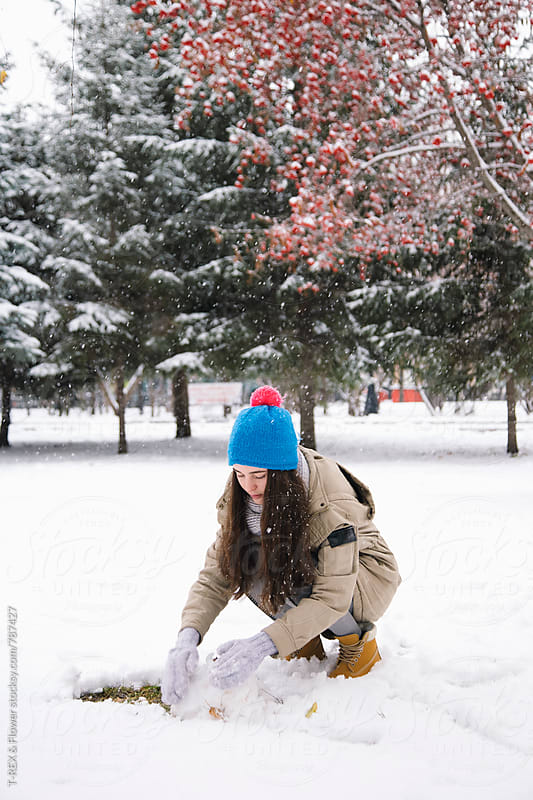 Young woman in winter clothes making snowman by T-REX & Flower for Stocksy United