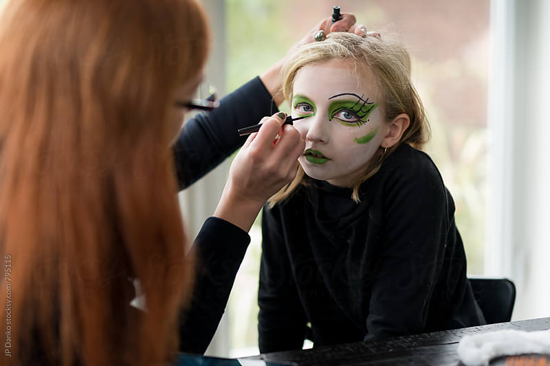 Mother Applying Face Paint Make Up for Girl Witch Halloween Costume by JP Danko for Stocksy United