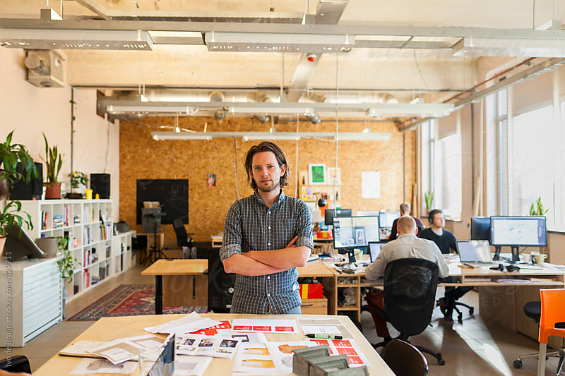 Young designer standing in his office, looking at the camera by Ivo de Bruijn for Stocksy United