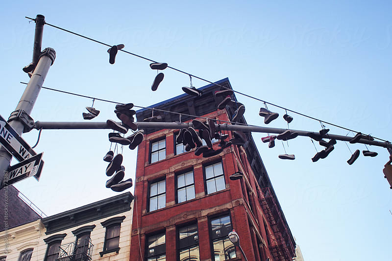 Tennis shoes and sneakers on a street wire in New York City. by Greg Schmigel for Stocksy United