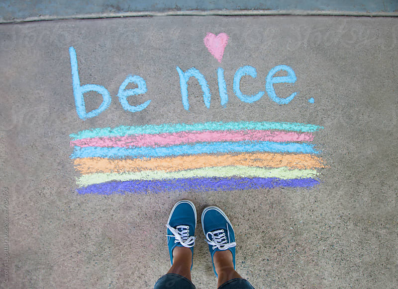 Feet standing above the words Be nice by Carolyn Lagattuta for Stocksy United