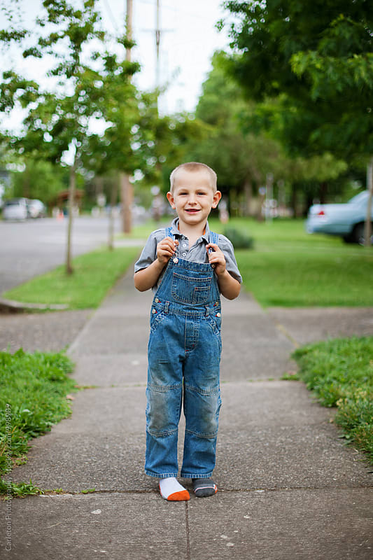Five year old boy in overalls and mismatched socks on sidewalk by Carleton Photography for Stocksy United