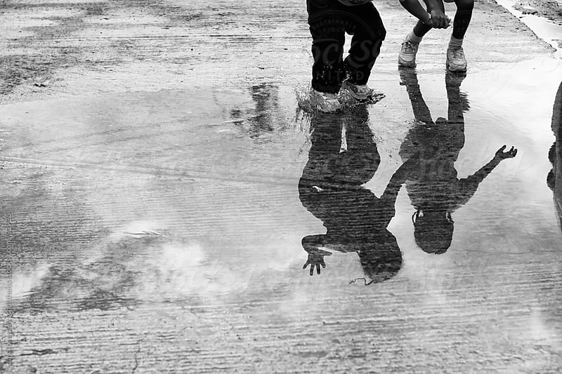 Shadow of two girls jumping in a water puddle by anya brewley schultheiss for Stocksy United