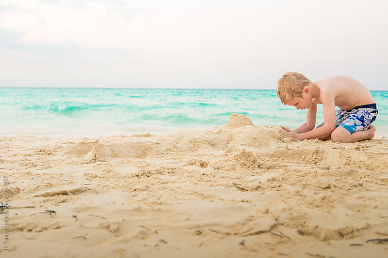 Boy Building Sand Castle on White Sand Tropical Beach WIth Turquoise Ocean on Vacation by JP Danko for Stocksy United