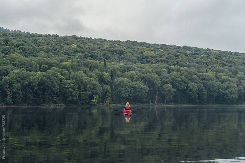 Woman in kayak on calm remote lake by Preappy for Stocksy United
