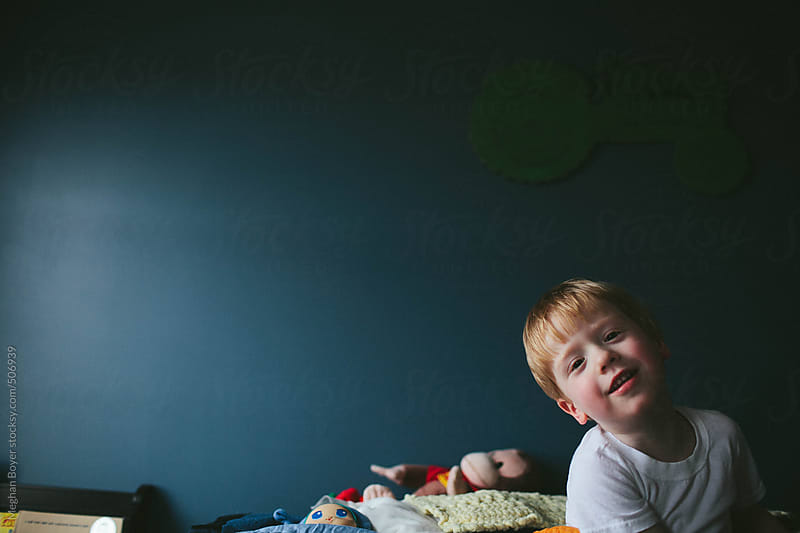 Boy just making up from a nap in a big bed by Meghan Boyer for Stocksy United