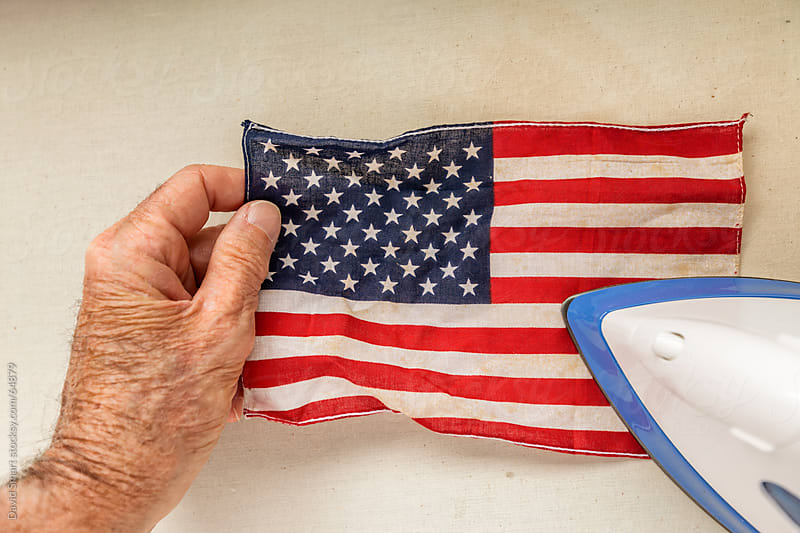 Pressing a small American Flag with an iron by David Smart for Stocksy United