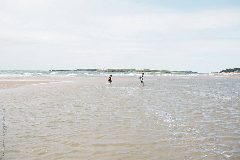 two boys on the beach by Léa Jones for Stocksy United