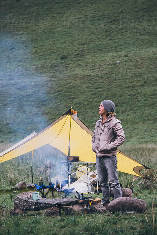 hiker outdoorsman standing by the fire in his mountain camp by Micky Wiswedel for Stocksy United