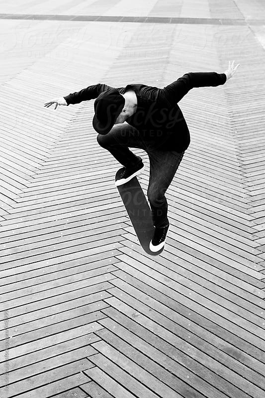 Skater doing a trick on the flat by Ivo de Bruijn for Stocksy United