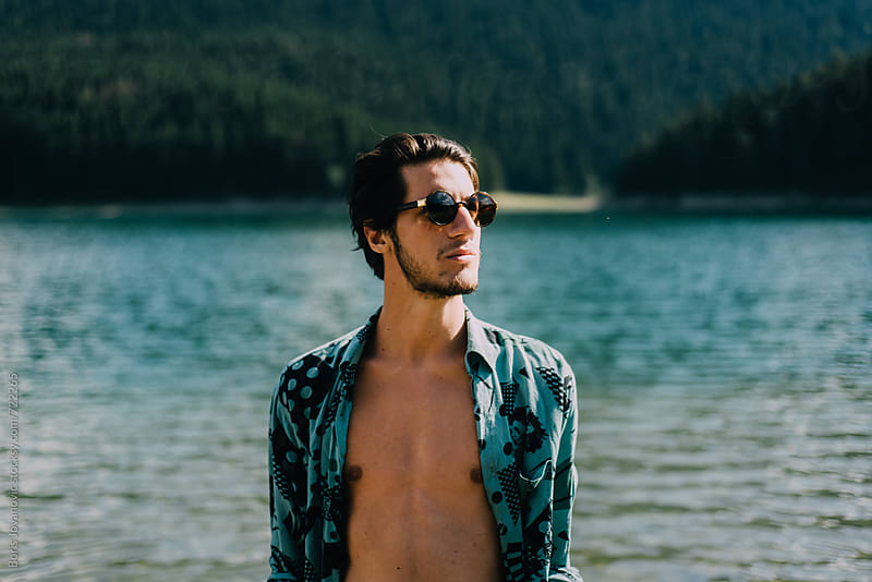 Portrait of young man against the lake by Boris Jovanovic for Stocksy United