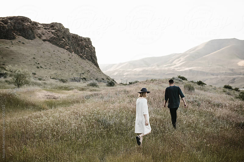 young fashionable couple walking through desert landscape by Nicole Mason for Stocksy United