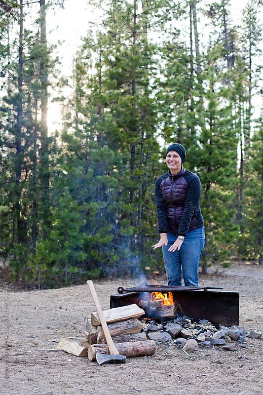 Woman standing next to campfire with chopped wood by Carleton Photography for Stocksy United