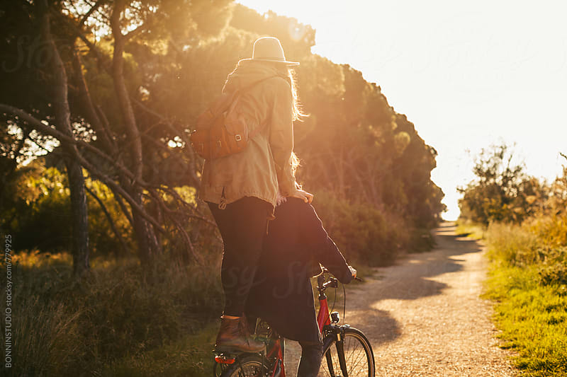 Back view of a hipster couple having fun on a bicycle in the forest. by BONNINSTUDIO for Stocksy United