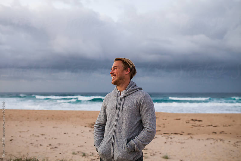 A man smiles and laughs at dawn on the beach by Reece McMillan for Stocksy United