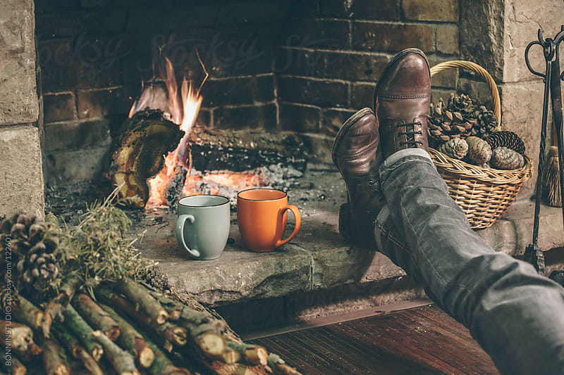 Man relaxing beside a fireplace in her comfortable home.  by BONNINSTUDIO for Stocksy United