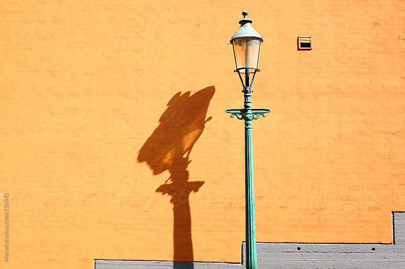 Old streetlantern and orange wall by Marcel for Stocksy United