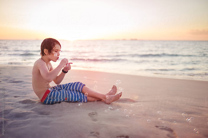 Boy blowing bubbles at the beach at sunset by Angela Lumsden for Stocksy United