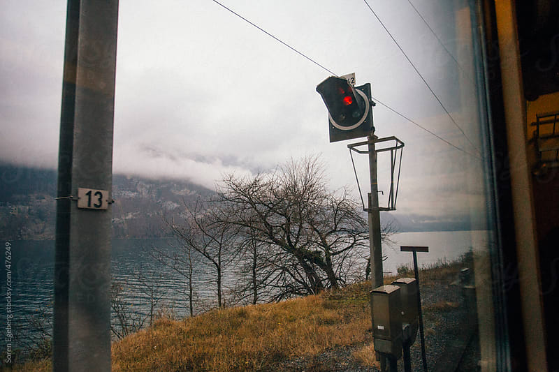 View of lake and red stop signal from train window near Walensee, Switzerland. by Soren Egeberg for Stocksy United