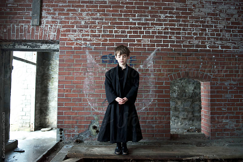 Boy stands quietly in abandoned building with eyes closed by Cara Dolan for Stocksy United