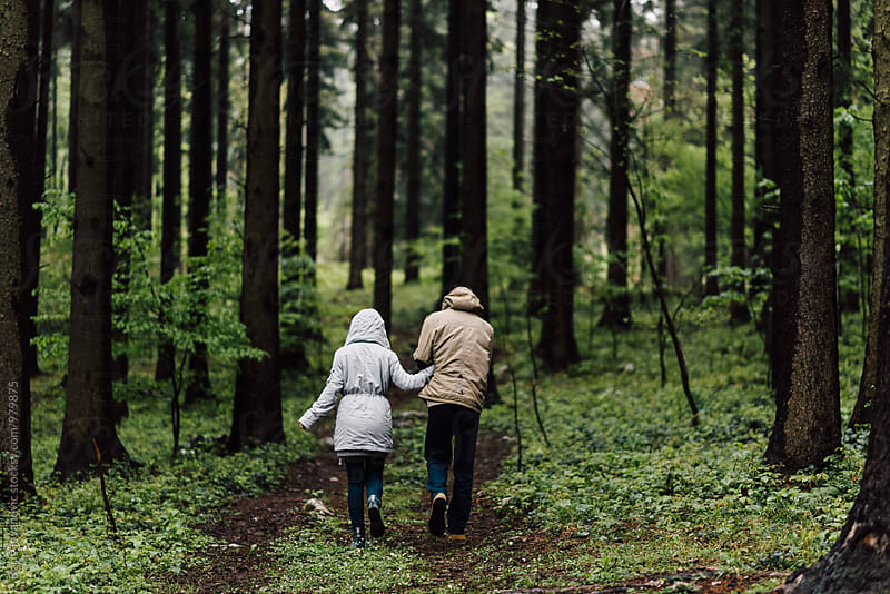 Couple walking down the forest road  by Boris Jovanovic for Stocksy United