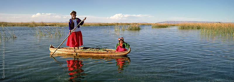 Uros Indian woman and traditional reed boat, Islas Flotantes, Lake Titicaca, Peru, South America by Gavin Hellier for Stocksy United