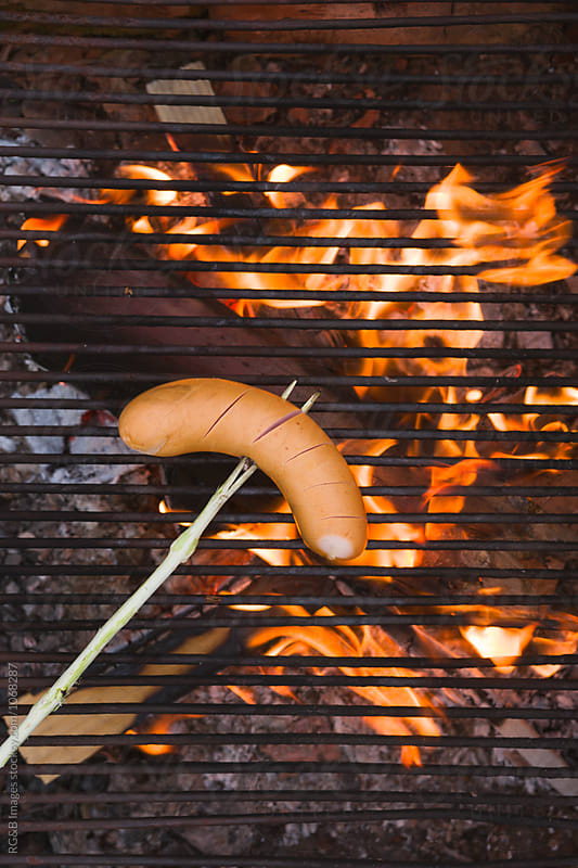 Sausage on a wooden stick grilling over camp fire by RG&B Images for Stocksy United