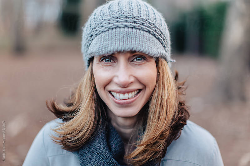 Close up portrait of a happy beautiful woman in a beanie by Jakob for Stocksy United