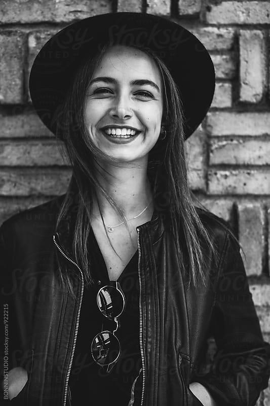 Portrait of a rocker woman smiling outside. by BONNINSTUDIO for Stocksy United